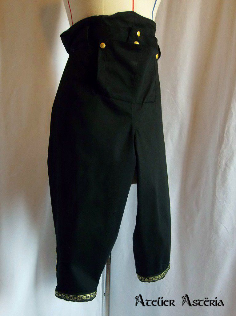 Culotte à pont personnalisée noire avec boutons dorés; les ouvertures aux genoux sont boutonnées comme les culottes historiques - Custom black half fall breeches with gold buttons; the openings at the knees are buttoned like the historical breeches